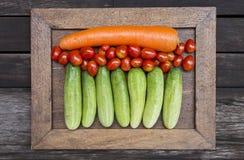 在葡萄酒木制框架的新鲜蔬菜在黑暗的木地板上 库存图片