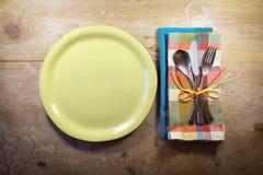 在葡萄酒木头桌上的明亮和五颜六色的偶然土气餐位餐具 免版税库存照片