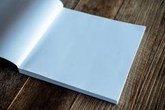在葡萄酒木桌上的一本白色空白的书 免版税图库摄影