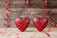 在葡萄酒木桌上的两闪烁心脏 圣徒情人节贺卡 2月14日背景 免版税库存图片