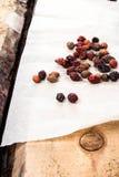 在葡萄酒木桌上的干玫瑰果 免版税库存图片