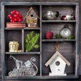 在葡萄酒木箱的圣诞节玩具:古色古香的时钟、鸟舍、球、丝带和雪橇圣诞老人议院 免版税图库摄影