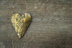 在葡萄酒木背景的土气金黄心脏装饰品 库存图片