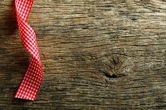 在葡萄酒木背景的方格的丝带 库存照片