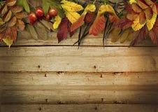 在葡萄酒木背景的秋叶边界 免版税库存图片