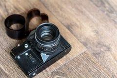 在葡萄酒木背景的老减速火箭的照相机与心脏爱卷筒软片 免版税库存照片
