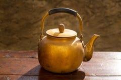 在葡萄酒木头桌上的古色古香的黄铜茶壶 库存照片