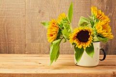 在葡萄酒杯子的向日葵在木桌上 免版税库存照片