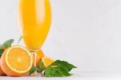 在葡萄酒杯的新鲜的橙汁用成熟半桔子和绿色叶子在软的白色木桌,拷贝空间,特写镜头上 图库摄影