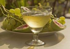 在葡萄酒杯的白葡萄酒在葡萄和无花果背景,阐明由太阳 库存图片