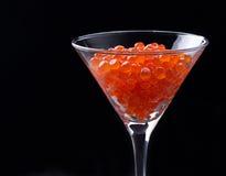 在葡萄酒杯的红色鱼子酱在黑背景 免版税库存照片