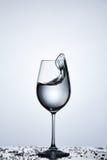 在葡萄酒杯的纯净的飞溅的水波,当站立在玻璃与装饰反对轻的背景时 库存照片