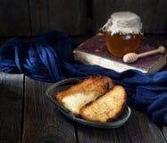 在葡萄酒板材、蜂蜜和书的酥脆多士在木背景 免版税图库摄影
