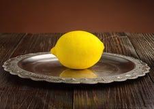 在葡萄酒板材正面图的新鲜的柠檬 免版税库存照片