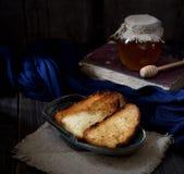 在葡萄酒板材,蜂蜜瓶子,在一块餐巾的匙子的酥脆多士在木背景 图库摄影