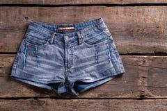 在葡萄酒架子的牛仔布短裤 免版税库存图片