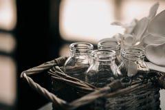 在葡萄酒柳条筐的玻璃瓶 在顶楼内部的装饰箱子 花被弄脏的blackground 定调子照片的葡萄酒 免版税库存照片