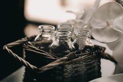 在葡萄酒柳条筐的玻璃瓶 在顶楼内部的装饰箱子 花被弄脏的blackground 定调子照片的葡萄酒 库存图片