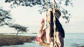 在葡萄酒样式打扮的女孩享用吹泡影 图库摄影
