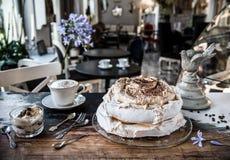 在葡萄酒桌上的蛋糕蛋白甜饼、点心和拿铁咖啡在一个减速火箭的样式的一个咖啡馆 免版税图库摄影