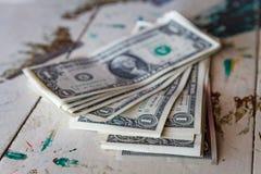 在葡萄酒桌上的金钱一美金 库存照片