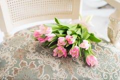 在葡萄酒椅子的桃红色郁金香花束 背景看板卡绿色风信花叶子百合Spring Valley 库存照片