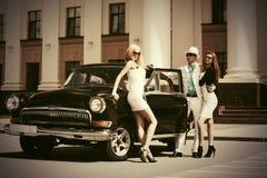 在葡萄酒汽车旁边的愉快的年轻时尚人民 库存图片
