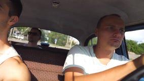 在葡萄酒汽车的三朋友驱动在乡下公路 坐在减速火箭的汽车前座的年轻人和 股票视频