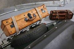 在葡萄酒汽车的后车箱的老皮革手提箱 免版税库存图片