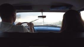 在葡萄酒汽车的年轻夫妇骑马在多雨下雨天期间 无法认出的坐在前座的男人和妇女  股票录像