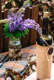 在葡萄酒瓶的羽扇豆在土气背景 库存图片