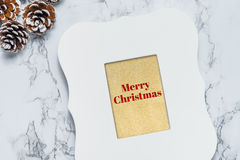 在葡萄酒白色画框的圣诞快乐文本与杉木co 免版税库存图片