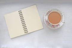 在葡萄酒的茶茶杯和笔记本有空白页的 免版税库存照片