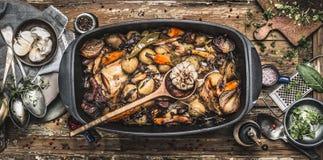 在葡萄酒砂锅的国家炖煮的食物与烹调匙子和烤菜在土气厨房用桌背景与工具 图库摄影