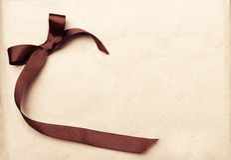 在葡萄酒礼品老纸背景的布朗丝带 库存图片