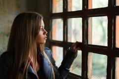 在葡萄酒窗口旁边的沉思白肤金发的妇女 库存图片