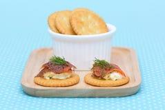 在葡萄酒背景的三文鱼乳脂干酪饼干 图库摄影