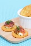 在葡萄酒背景的三文鱼乳脂干酪饼干 免版税图库摄影