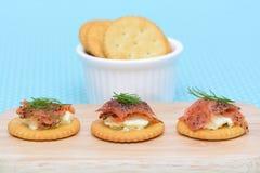 在葡萄酒背景的三文鱼乳脂干酪饼干 库存图片
