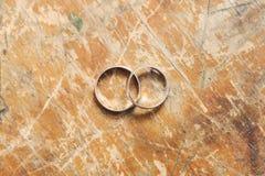 在葡萄酒背景的两个金子婚戒 库存图片