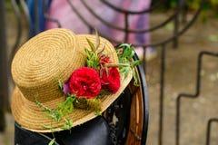 在葡萄酒草帽的选择聚焦有红色花的妇女的 库存图片