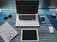 在葡萄酒蓝色木桌是一台个人计算机计算机、一种片剂和一个笔记本纪录的 库存图片