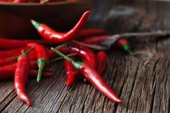 在葡萄酒银叉子的炽热辣椒在红色背景 免版税库存图片