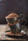 在葡萄酒银杯子的红色米在年迈的木背景 选择聚焦 免版税库存照片