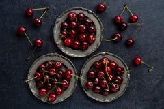 在葡萄酒银盘的新鲜的樱桃在黑暗的难看的东西背景 图库摄影