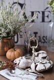 在葡萄酒银色盘子的巧克力蛋白甜饼反对石南花背景 库存照片
