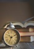 在葡萄酒闹钟和开放书背景wi的罗马数字 免版税库存图片