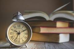 在葡萄酒闹钟和开放书背景wi的罗马数字 库存图片