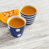 在葡萄酒陶瓷杯子的新鲜的南瓜汁 免版税库存照片