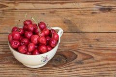 在葡萄酒陶瓷碗的有机本地出产的樱桃,在木背景 免版税库存照片
